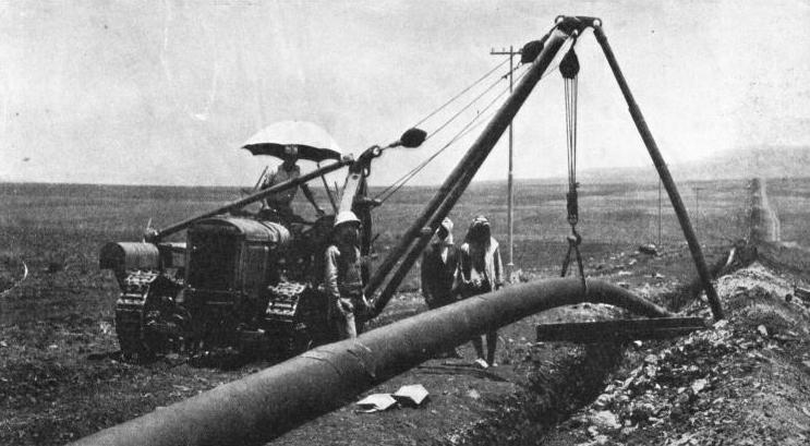 LOWERING A SECTION OF THE IRAQ PIPE LINE into its trench