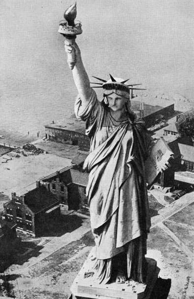 OVER 300 FEET ABOVE THE GROUND, the torch held in the right hand of the figure of Liberty is reached by a staircase inside the colossal monument